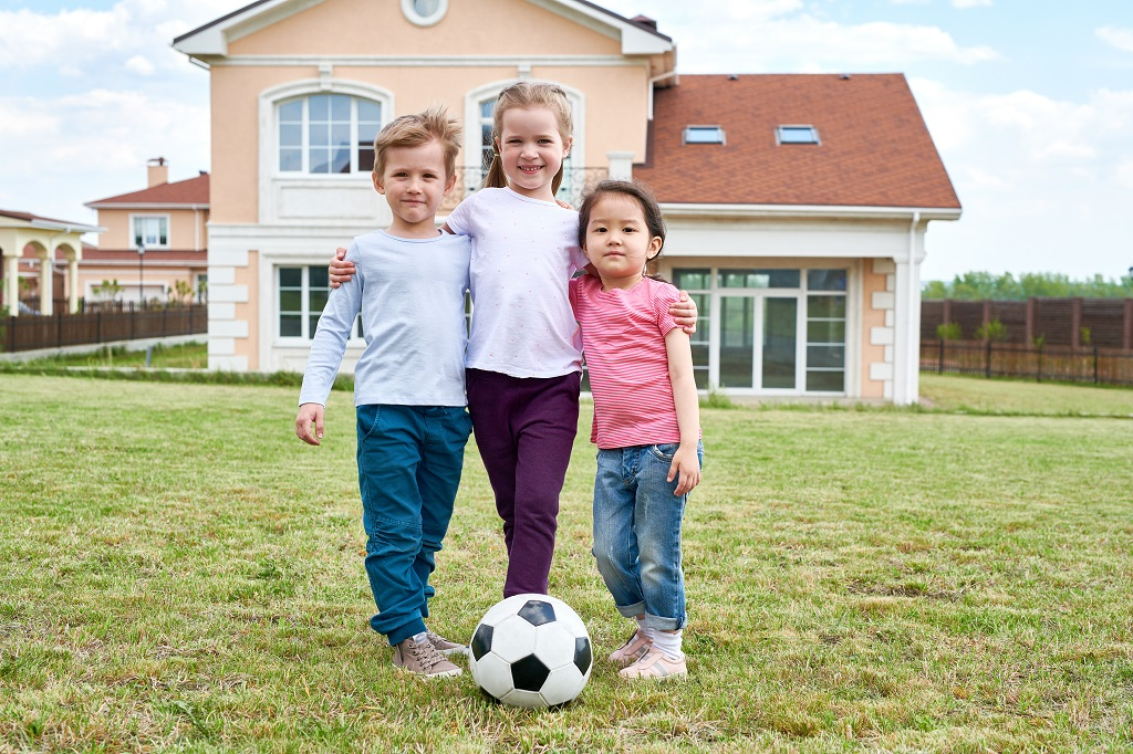 kids playing soccer on lawn